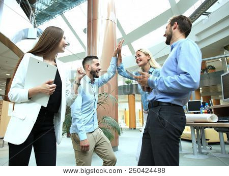Happy Young People Standing In Office And Giving High Five To Their Colleagues