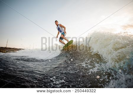 Young active brunet riding on the wakeboard on high wave of motorboat, having healthy summertime poster