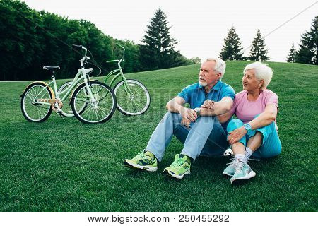 Happy Senior Couple Sits On The Grass, Enjoying The Rest After Riding Bicycles. Bicycles Stand Near