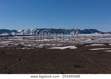 Volcanic landscape in Northern Iceland at springtime. Melting snow from the vast fields of volcanic rocks and mountains ridge. poster