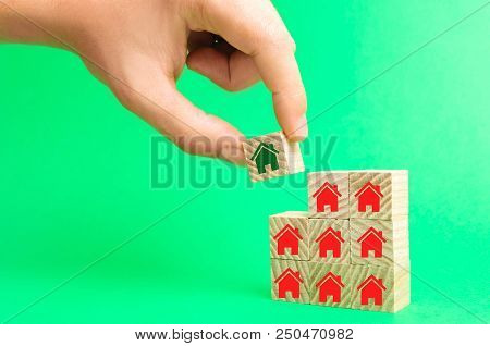 The Businessman's Hand And Wooden Cubes With Houses. Investment In Real Estate. Buildin, Sale, Rent,