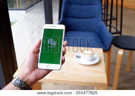 A Man Sit In Cafe Holding Mobile With Wechat Screen