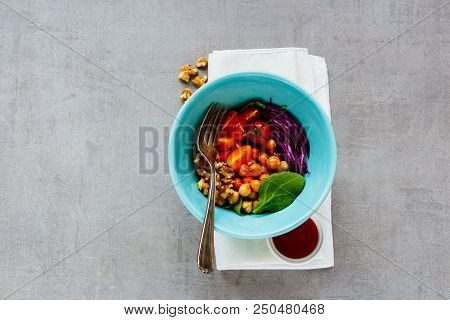 Healthy Vegan Buddha Bowl With Chickpeas, Spinach, Tomatoes, Red Cabbage, Walnuts And Honey Dressing