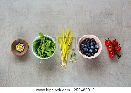 Various Raw Organic Food: Arugula, Cress Salad, Blueberries, Cherry Tomatoes, Pine Nuts Over Light B