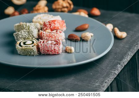 Traditional Oriental Sweets And Nuts: Hazelnuts, Cashews On A Dark Wooden Background. Turkish Desser