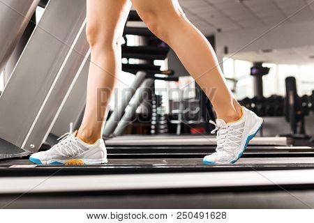 Close Up Girls Legs Walking At The Treadmill In The Gym Over Sunrise. Wearing In White Orange Blue S