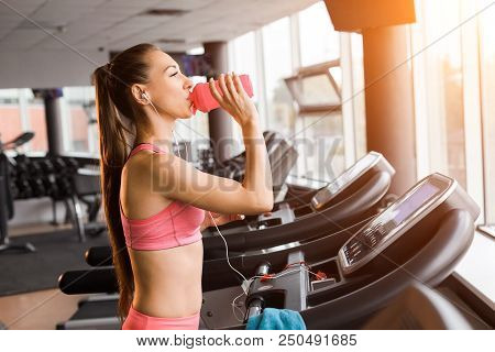 Slim Pretty Joyful Girl Jogging At The Treadmill And Drinking A Shaker With Protein Cocktail In The