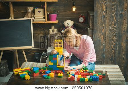 Building Concept. Mother And Son Play With Building Blocks. Mother And Child Build Structure With To