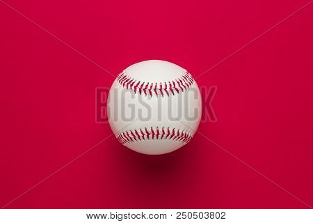 Top View Of Baseball Ball. Baseball Ball On Red Background. Minimalistic Photo Of Baseball Ball. New
