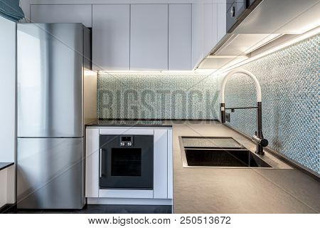Moscow - March 25, 2018: Modern Interior Of Kitchen In Small Apartment. Pearlescent Fine Tiles In Wh