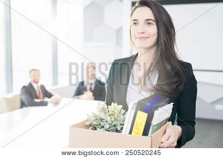 Waist Up Portrait Of Smiling Young Businesswoman Holding Box Of Personal Belongings  Leaving Office