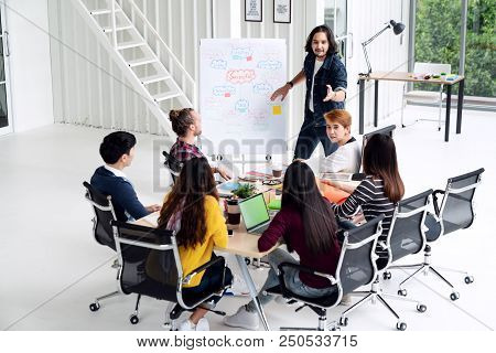 Young Asian Creative Man Standing And Making Presentation At Modern Office Happy Talking And Brainst
