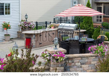 Upscale Outdoor Patio With Kitchen Area And Comfortable Wicker Furniture In The Shade Of A Striped U