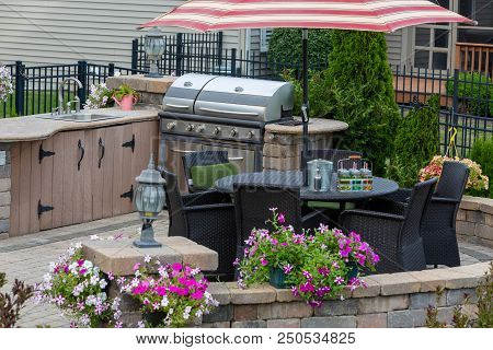 Brick Patio With Gas Bbq In An Outdoor Kitchen And Dining Seating Under A Striped Umbrella Surrounde