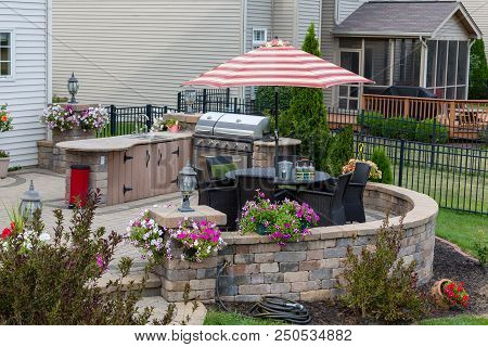 Upscale Backyard Round Brick Patio With Outdoor Kitchen Fitted With A Gas Barbecue And Wicker Dining