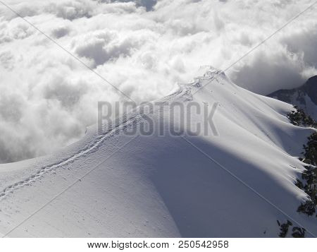 narrow and exposed mountain summit ridge with tracks of climbers leading to a sea of clouds poster
