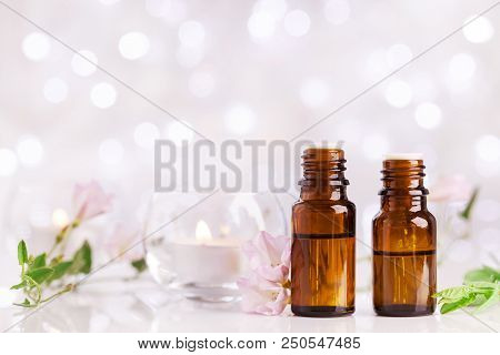 Two Bottles With Essential Oil, Flowers And Candles On White Table With Bokeh Effect. Spa, Aromather