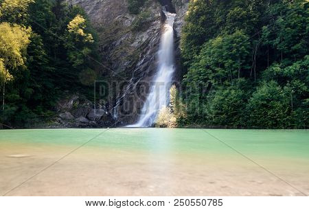 Waterfall In Midst Of Forest Landscape Cascading Into A Colorful Turquoise And Brown Pond