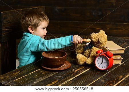Friend And Friendship. Little Boy Feed Toy Friend From Spoon. Child Have Dinner With Teddy Bear Frie