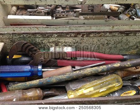 Assortment Of Old, Used Screwdrivers And Other Tools In A Metal Tool Box In An Engineering Workshop