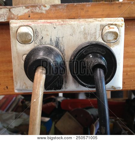 Old Electrical Plugs And Cables In A Dirty Electricity Socket In A Tradesman's Workshop