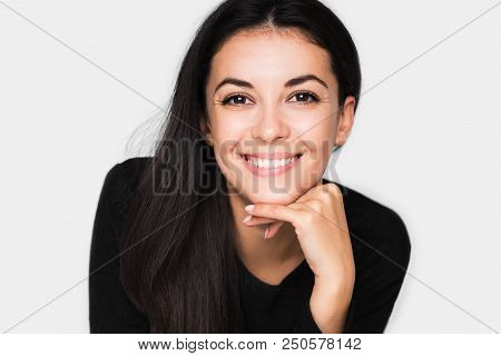 Portrait Of Brunette Cute Woman With Beautiful And Healthy Toothy Smile, With Hand On Chin. Young Ha