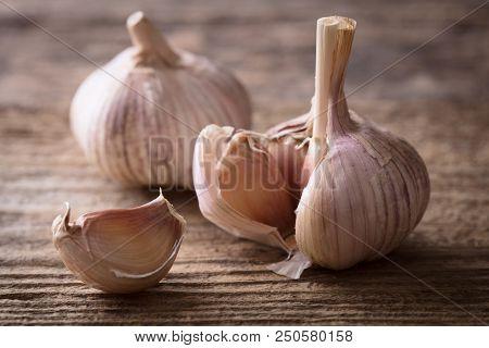 Few Pieces Of Garlic On Wooden Background