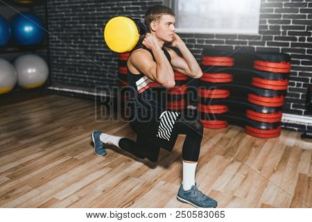 Handsome Sportsman With Sandbag On Shoulders While Exercises In The Gym. Attractive Athletic Male Do