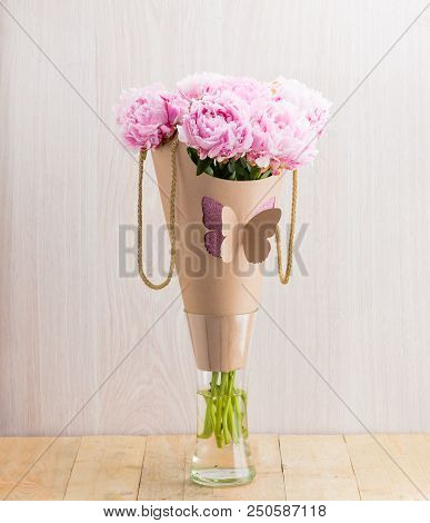 Beautiful Bouquet Of Pink Peonies Wrapped In Paper For Present In Crystal Vase On Wooden Table
