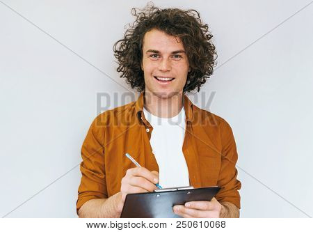 Horizontal Shot Of Handsome Male Student With Curly Hair, Writes In Diary Plan For Next Week, Wearin