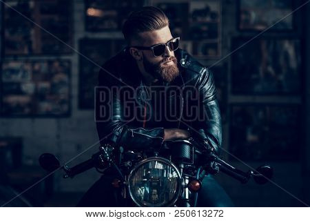 Young Bearded Biker Sitting On Motorcycle In Garage. Indoor Garage. Young Mechanic In Garage. Parts