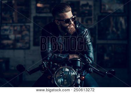 Young Bearded Biker Sitting On Motorcycle In Garage. Indoor Garage. Young Mechanic In Garage. Parts