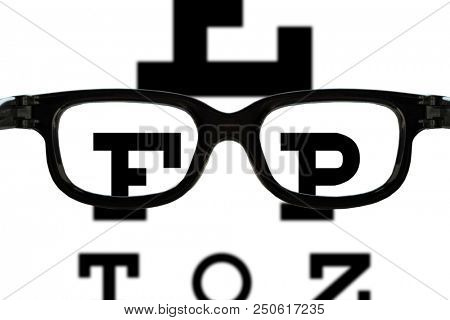 glasses in front of an eye sight test chart with blurry and sharp areas