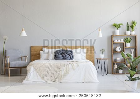 Blue Knot Pillow On Wooden Bed In Modern Bedroom Interior With Patterned Armchair. Real Photo