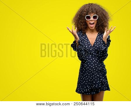 African american woman with sunglasses and summer dress very happy and excited, winner expression celebrating victory screaming with big smile and raised hands