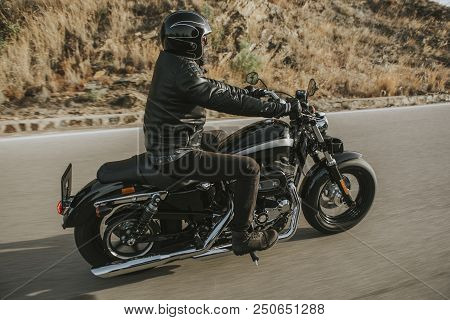 Side View Of Classic Motorbike Rider Riding An American Classic Motorcycle.