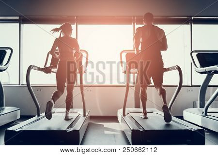 Bearded Man And Young Woman On Treadmills In Gym. Man With Athletic Body. Healthy Lifestyle And Spor