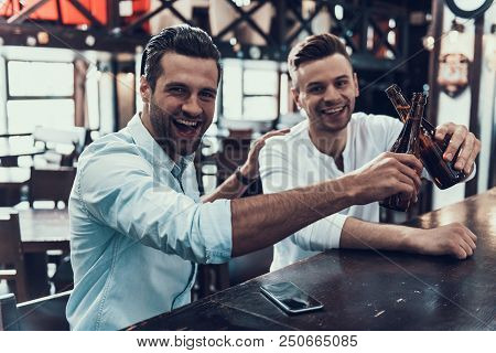Young Smiling Men Drinking Beer In Modern Bar. Sitting In Pub. Bottle Of Beer. Young Men With Beer.