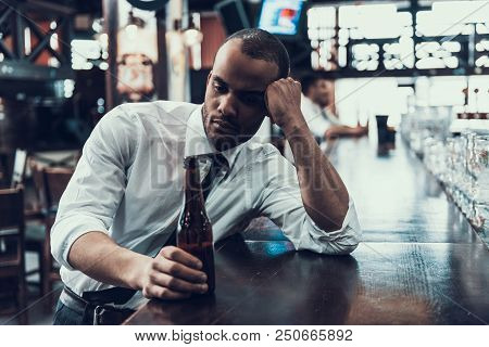 Sad Young Man With Bottle Of Beer Sitting In Bar. Drunken Guy In Modern Pub. Unhealthy Lifestyle. Ad