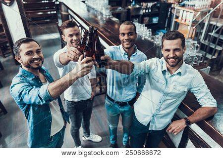 Smiling Young Men Drinking Beer And Have Fun. Sitting In Pub. Bottle Of Beer. Young Men With Beer. M