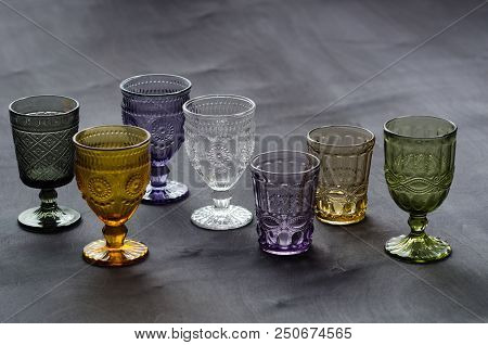 A Set Of Transparent, Crystal Glasses Of Different Colors, On A Dark Wood Table.