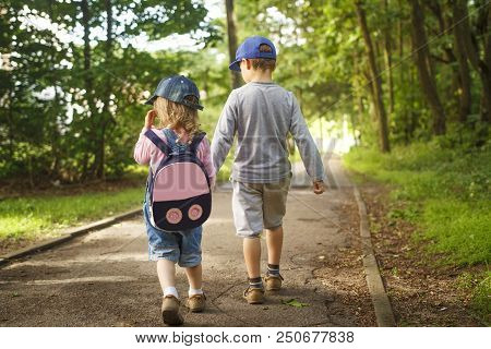 Little Friends Children Hold Hands And Walk Along Path In Park On Summer Day. Boy And Girl Are Walki