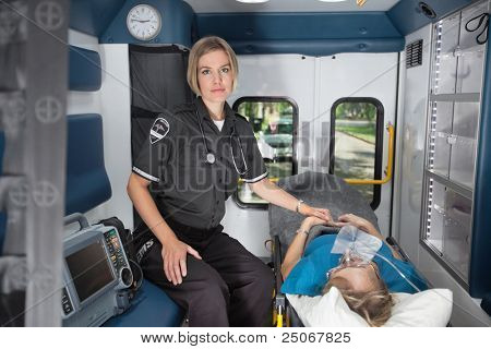 Serious emergency medical professional in ambulance with senior female patient