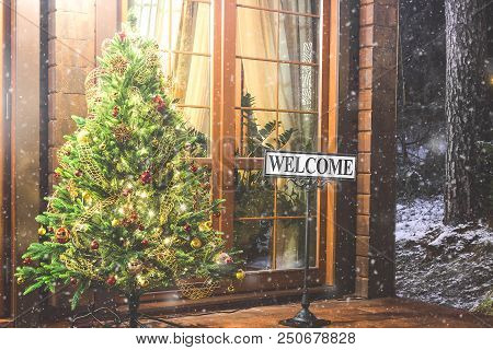 Christmas Tree With Welcome Inscription Outside. Evening Street House Entrance And Christmas Tree Wi