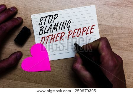 Handwriting text writing Stop Blaming Other People. Concept meaning Do not make excuses assume your faults guilt Written on notepad hand hold marker with love heart wooden background poster