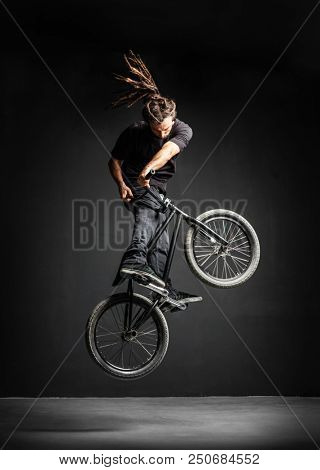 A man doing an extreme stunt on his BMX bicycle. Professional rider. Sport. poster