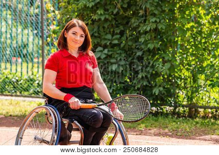 Disabled Young Woman On Wheelchair Playing Tennis On Tennis Court