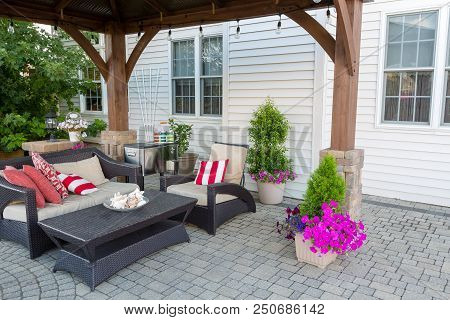 Outdoor Living Space On A Brick Patio With Covered Gazebo And Comfortable Furniture With Colorful St