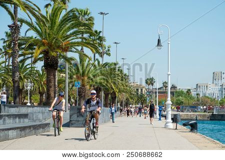 BARCELONA, SPAIN - APRIL 27, 2018: People walking and riding bicycles by the seafront at the Port Vell, the Old Port of Barcelona, Spain