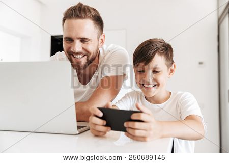 Portrait of a cheerful young father and his son having fun time together at home while using laptop and playing games on mobile phone